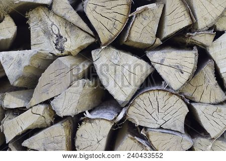 Chopped Firewood On A Stack, Prepared For Winter. Photo Depicts A Backdrop With Birch Firewood In A