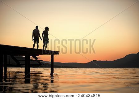 Silhouette Of Sensual Couple Stand On Pier With Sunset Above Sea Surface On Background. Couple In Lo