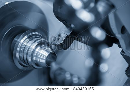 The Cnc Lathe Machine Or Turning Machine Cutting The Metal Cone Shape Part In The Light Blue Scene.
