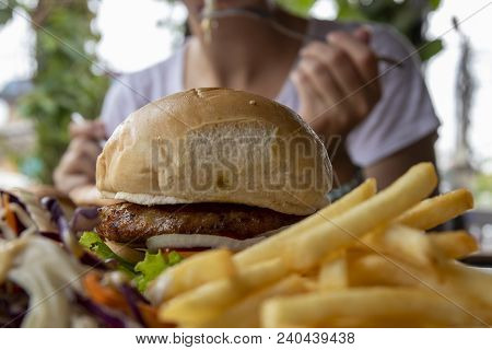 Burger And French Fries Closeup Photo With Eating Woman On Background. Restaurant Lunch With Beef Bu