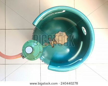 Green Lpg Cooking Gas Tank Or Propane Cylinder With Safety Valve And Regulator In Household, Top Vie