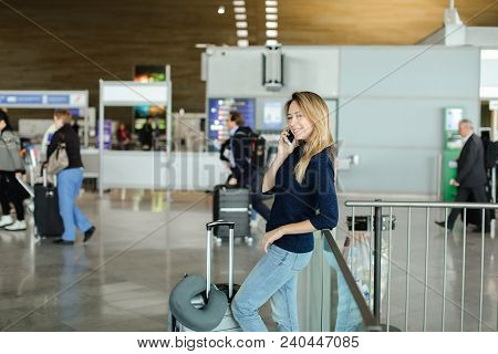 Pretty Young Woman Speaking By Smarphone At Airport Hall With Valise. Concept Of Modern Technology A