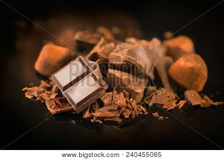 Assorted Chocolate Candies. Chocolate Sweets. Candy Design over dark Background. Various Chocolates. Confectionery poster