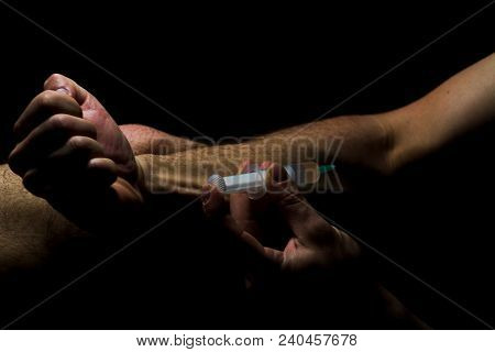 A Dark Photo Of A Young Man Who Injects The Drug Into A Vein.detail Of The Arm Of A  Junkie Who Inje