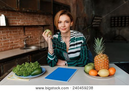 Gorgeous Healthy Young Woman Eating Apple In Her Modern Loft Kitchen. Fitness Coach. Eat Right To Ke