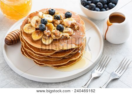 Stack Of Pancakes With Banana, Blueberries, Walnuts, Honey And Caramel Sauce On White Plate. Closeup