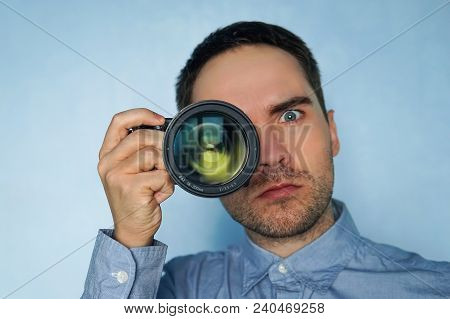 Close Up Photo Of Man In Hat On Blue Background Taking A Photo With Digital Mirrorless Camera. Young