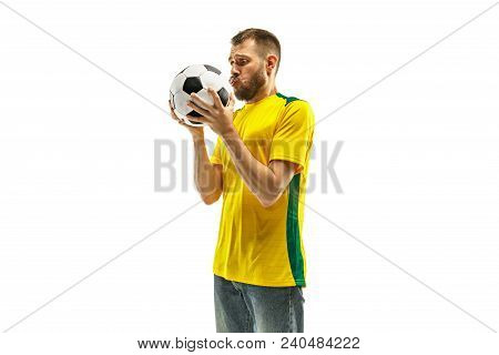 Brazilian Fan Celebrating On White Background. The Young Man In Soccer Football Uniform Kissing Ball