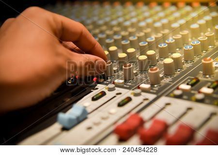 Close-up Hands Of Sound Engineer Adjusting Audio Mixer Controller For Live Music And Studio Equipmen