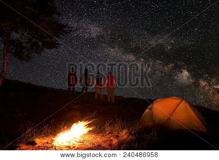Back View Of Two Pair Hikers Holding Hands And Enjoying Milky Way At Starry Sky During A Night Of Ca