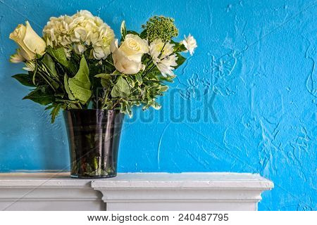 A Bouquet Of Flowers Sits In A Vase On The Mantle Of A Fireplace Against A Blue Wall.