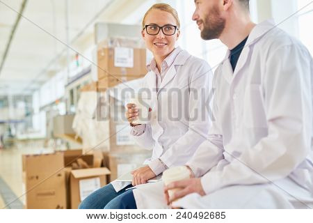 Bearded technologist and his pretty colleague drinking cappuccino from paper cups and talking to each other while taking short break from work, interior of packaging department on background poster