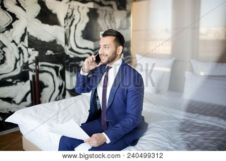 Young cheerful economist in formalwear sitting on bed in hotel room and talking to clients on smartphone