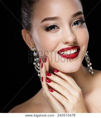 Beautiful brunette woman with bright make-up and jewelry earrings smiling close-up. Red lips and nails, evening make-up, luxurious look.