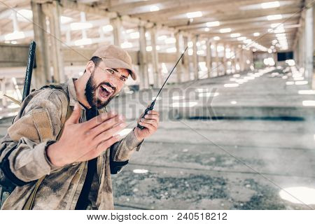 A Picture Of Lonely Bearded Man In Hangar. He Is Holding Portable Radio In Left Hand And Using It. G