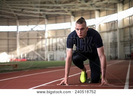 A Shot Of Young Athlete At Starting Position Ready To Start A Race.sprinter Ready For Race