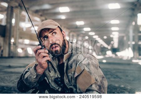 A Picture Of Handome And Attractive Soldier Speaking Into Portable Radio. He Is Looking To The Right