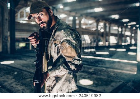 A Picture Of Military Man Posing On Camera. He Is In A Big Hangar. He Is Holding Black Rifle And Rea