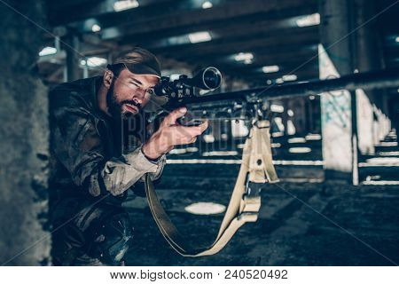 View Of Warrior Sitting Close To The Ground And Waiting. He Is Taking Aim By Looking Through Lens On