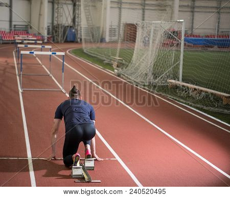 Rear View Of An Male Track And Field Athlete Preparing Hurdling.start Positon From The Blocks