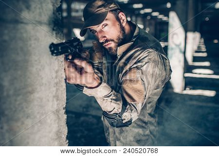 Concentrated And Serious Man Is Looking Through Lens Straight Forward. He Is Taking Aim. Warrior Is