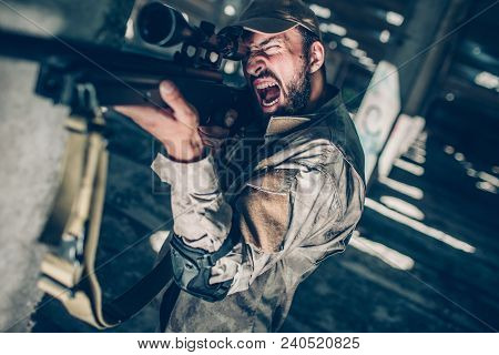 Soldier Is Creaming. He Is Looking Through Lens Because He Is Taking Aim. Guy Is Redady To Shoot Fro