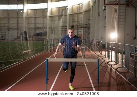 The Shot Of Concentrated Male Track And Field Athlete Hurdling.indoor Training