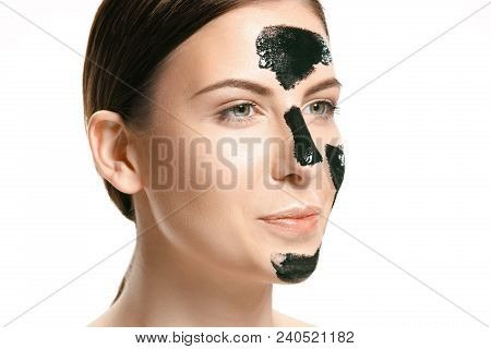 Young Beautiful Caucasian Woman Applying A Black Cosmetic Mask For The Face Of The Therapeutic Black