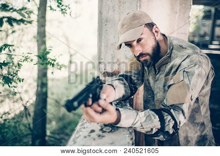 Concentrated And Courageous Man Is Standing Near Exit And Holding Gun In His Hands. Man Is Holding F