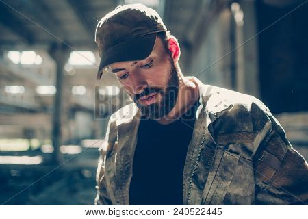 Portrait Of Terrorist. He Is Looking Down. Guy Is Standing In A Big And Empty Hangar In A Sunny Day