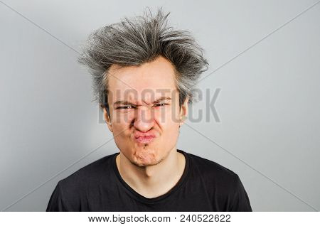 Unshorn And Unshaven Young Guy With An Emotion Of Disgust On His Face, On Gray Background.