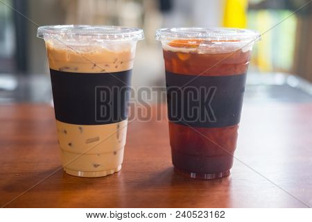 Cup Of Iced Black Coffee Americano And Iced Coffee Latte On Wooden At A Hot Day