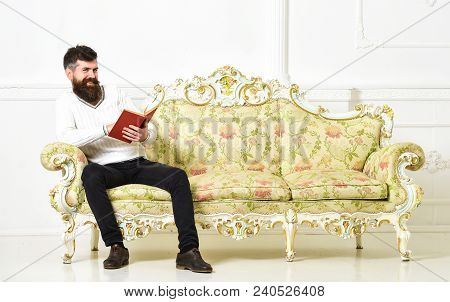 Man With Beard And Mustache Sits On Baroque Style Sofa, Holds Book, White Wall Background. Macho On