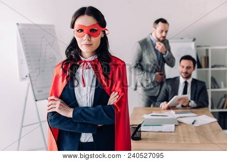 Super Businesswoman In Cape Standing With Crossed Arms In Office