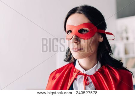 Portrait Of Attractive Super Businesswoman In Cape And Mask Looking Away In Office