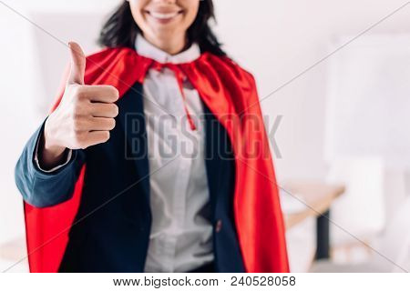 Cropped Image Of Super Businesswoman In Cape Showing Thumb Up In Office