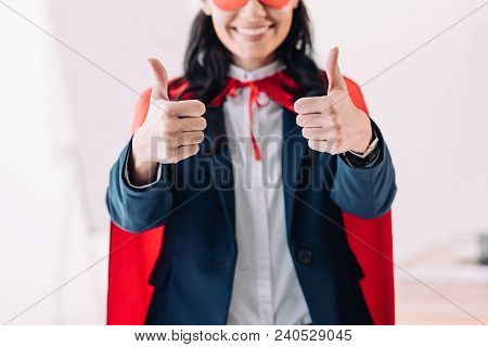 Cropped Image Of Super Businesswoman In Cape And Mask Showing Thumbs Up In Office