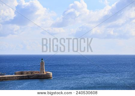 St. Elmo's lighthouse at Valletta, Malta. Breakwater of grand harbour between blue sea and cloudy sky background.
