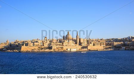 Valletta, Malta. Panoramic view of the historic island under a clear blue sky, the dome of Carmelite Church and St Paul`s tower.
