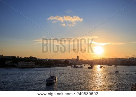 Malta, Valletta. Sliema town, sea and sky with few clouds at sunrise, sunset. Sun paints the sea and the sky with many colors background. Panoramic view.