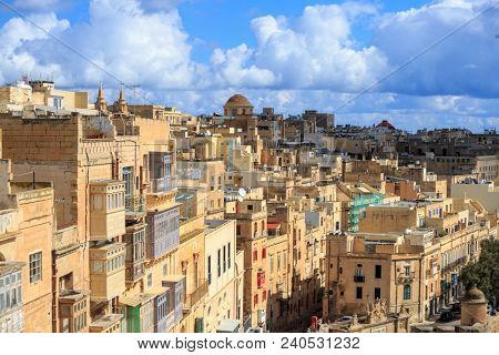 Malta, Valletta. Capital with tall traditional limestone buildings and covered balconies, under a blue sky with few clouds.