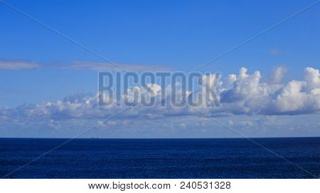 A ship is traveling in calm sea to an exotic destination. Blue sky with fluffy clouds background. Cruise on summertime for vacation.