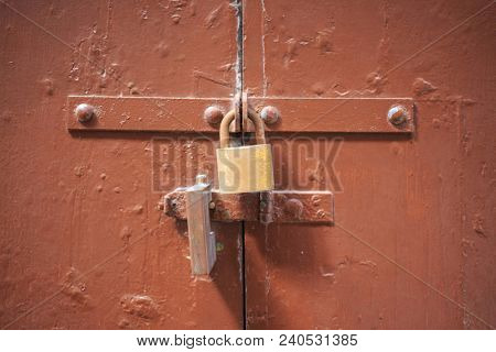 Wooden brown door background locked with two padlocks. Timeworn entrance provides safety and privacy. Close up view with details.