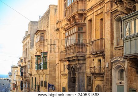 Malta, Valletta, traditional sandstone buildings with colorful wooden windows on covered balconies. Blue sky with clouds and sea background.