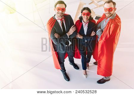 High Angle View Of Super Businesspeople In Masks And Capes With Crossed Arms Looking At Camera In Of