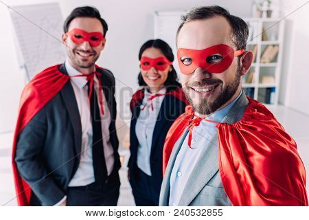 Smiling Super Businesspeople In Masks And Capes Looking At Camera In Office