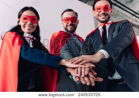 Low Angle View Of Super Businesspeople In Masks And Capes Putting Hands Together In Office