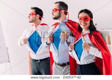 Super Businesspeople In Masks And Capes Showing Blue Shirts In Office