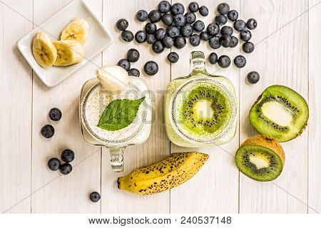 Banana And Kiwi Milkshakes In Mason Jars With Creme And Decorations On Top And Decorated With Bluebe