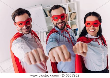Super Businesspeople In Masks And Capes Showing Fists In Office